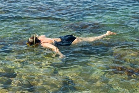 Adult woman diving into clear water of sea near a shore