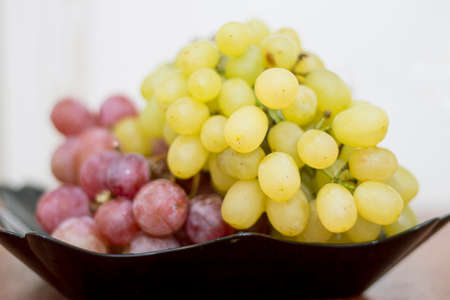 Red and White wine bunch of grapes in the black plate ready to eat