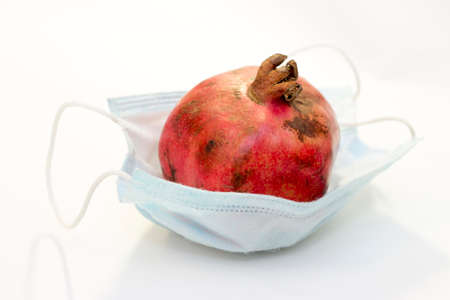 One red pomegranate lies in a protective medical mask isolated on a white background. Coronavirus protection concept