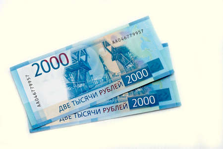 Scattered Russian 2000 rubles new banknotes closeup isolated on the white background