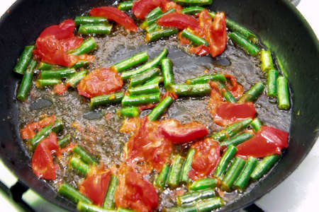 Tomato and green beans roasted on the black frying pan for morning roasted whole eggs closeup