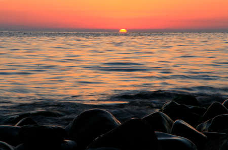 A subtropical sunset over sea in red colors. Tha Black sea seashore
