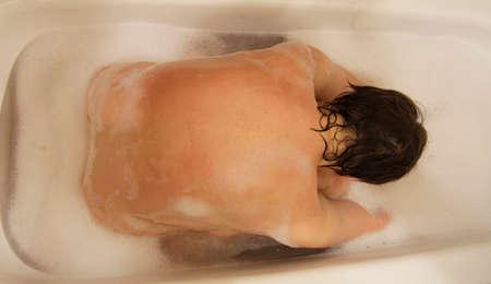 Female taking a bath in the bathroom top view