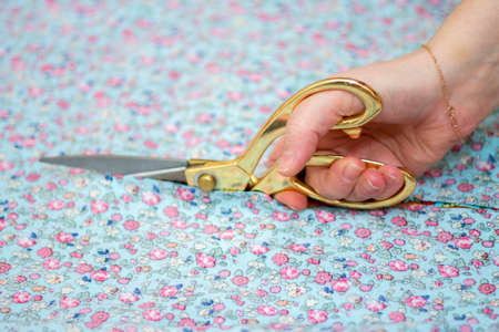 Woman cutting the colorful facbric in workshop by scissors