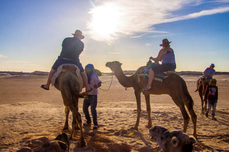 Group of tourists over dromedary camels walking in the sands of Sahara desert, Tunisia, North Africa 13 october 2018