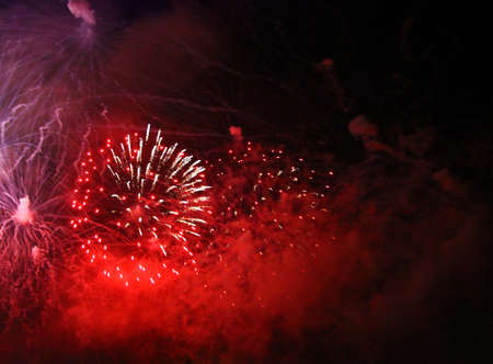 The Celebration red colored firework flashing in the black night sky background