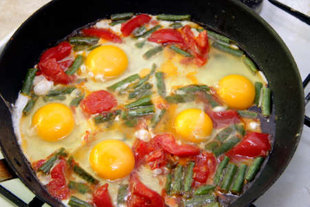 Morning roasted whole eggs on the black plate and with tomato and green beans closeup Standard-Bild
