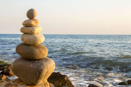 Balanced stones on the seashore summertime and sea waves background
