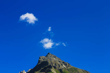 The Caucasus Mountains Peaks Under Snow And Clear Blue Sky with small white clouds Dombai summer time Standard-Bild