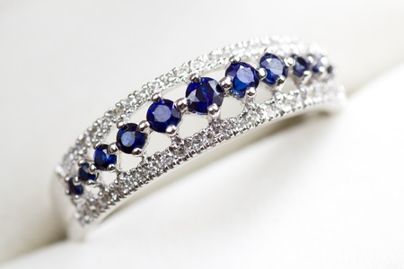 A white gold engagement ring with diamond and sapphire in a box.