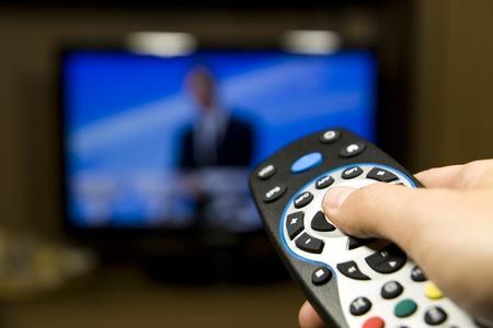 Mano que sostiene el control remoto de la TV con un televisor en el fondo. De cerca. Foto de archivo