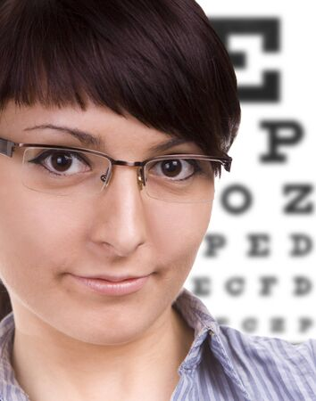 Beautiful young woman wears trendy glasses. Eye chart in background. Stock Photo - 10494806