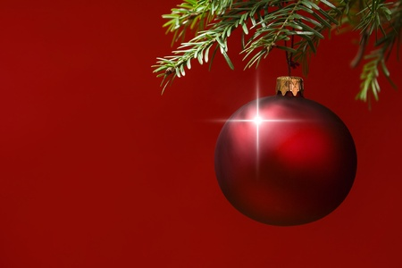 knack: Red Christmas ornament hanging, with copy space to the left. red background