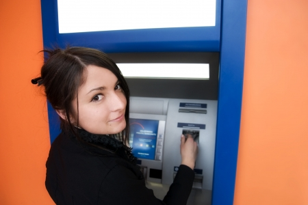 automatic teller machine bank: Woman withdrawing money from credit card at ATM