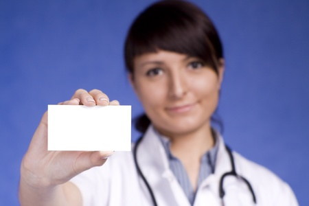 Women Doctor holding blank business card. Focus on fingers and card. photo
