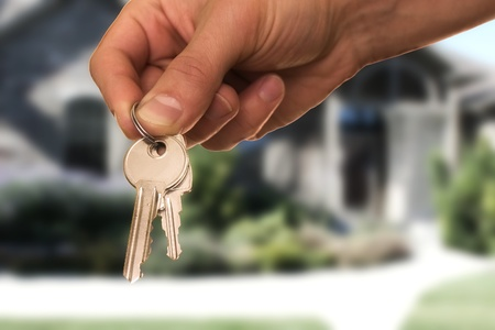 hand holding keys, house in the background Stock Photo