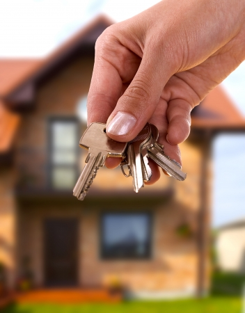 buying a house: handing keys in the house background Stock Photo