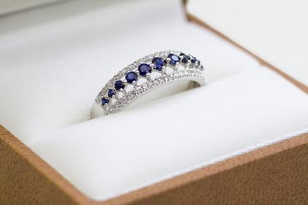 zafiro: Un oro blanco anillo de compromiso con diamantes y zafiros en una caja.