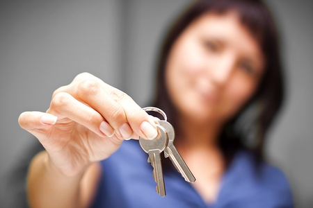 Realtor is giving the keys to an apartment to some clients – focus on the keys Stock Photo