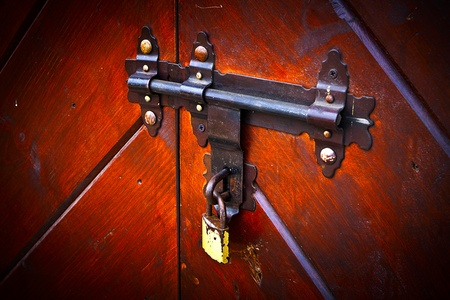Rusty old lock, latch on wooden closed door with a modern padlock. Stock Photo - 10687273