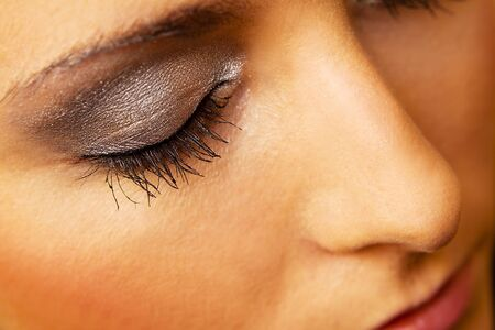 close up eyes: Woman eye with extremely long eyelashes and golden makeup Stock Photo