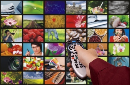 Close up of a hand holding a remote control with a television concept. Stock Photo - 10683307