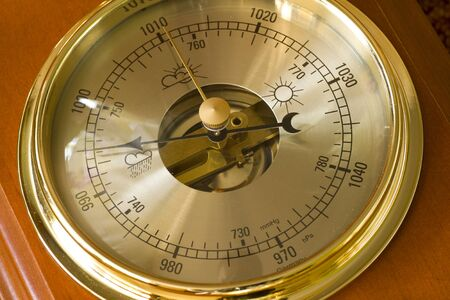 barometer: A close up of a barometer pointing towards the hurricane setting.