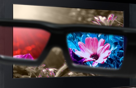 high definition: Glasses 3D in front of the TV with a flower. 3D television.