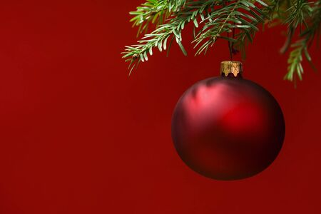 Red Christmas ornament hanging, with copy space to the left. red background photo