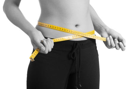 woman measuring waist: Woman standing pulling measuring tape around waist.