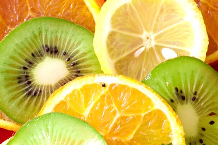 overlapped: Ripe fruit slices overlapped background (lemon, kiwi, tangerine, orange) Studio shot.
