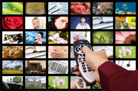 multi media: Close up of a hand holding a remote control with a television concept.