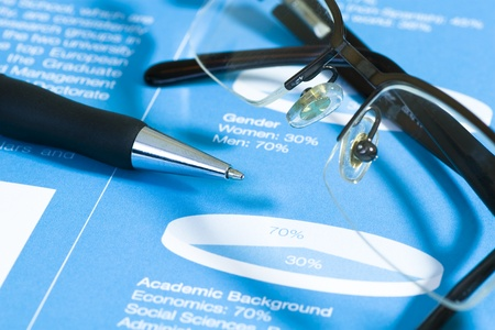 Fountain pen and glasses on stock chart on blue report. Shot in studio. Stock Photo - 11157531
