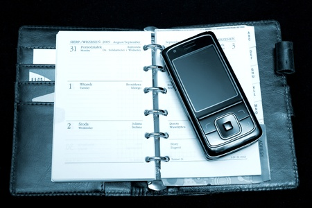 notebook, calendar and phone in black background photo