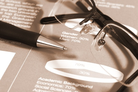 Fountain pen and glasses on stock chart on blue report. Shot in studio. photo