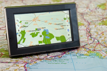 Portable GPS for a car sitting on a map Stock Photo - 11929461