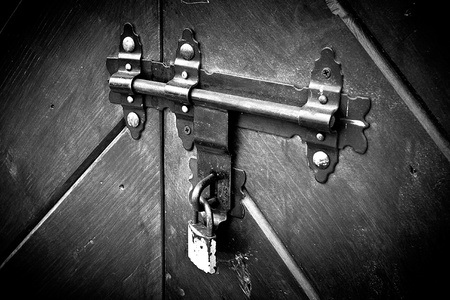 Rusty old lock, latch on wooden closed door with a modern padlock.  photo