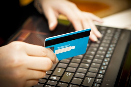 Hands entering credit card information into a laptop photo
