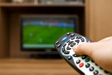 Hand holding TV remote control with a television football. Stock Photo