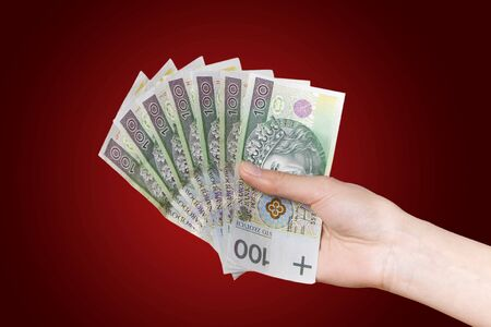 Hand with polish money on red background photo