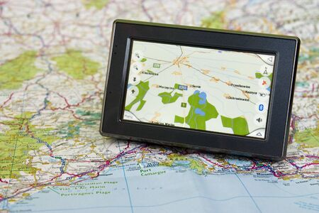 Portable GPS for a car sitting on a map Stock Photo - 12054837