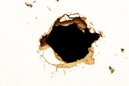 bullet hole: Hole in the fibreboard on black background.