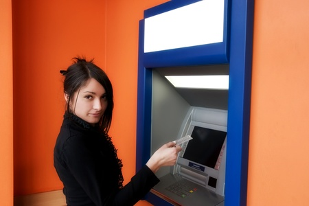 Woman withdrawing money from credit card at ATM Stock Photo - 12880763