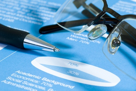Fountain pen and glasses on stock chart on blue report  Shot in studio Stock Photo - 13022903