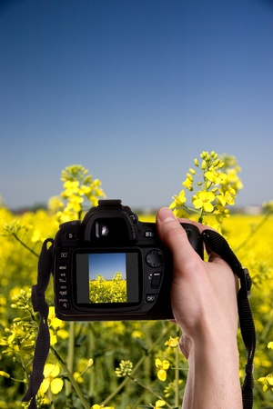 Man taking a landscape photography with a digital photo camera photo