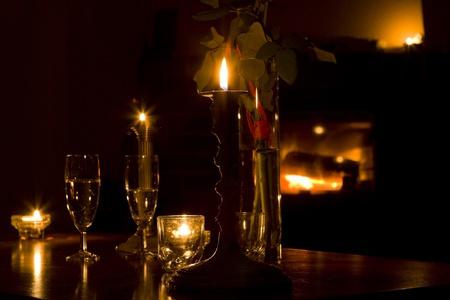 Glasses of champagne and candles: ly rượu trước lò sưởi, ngọn lửa tự nhiên như là một nền