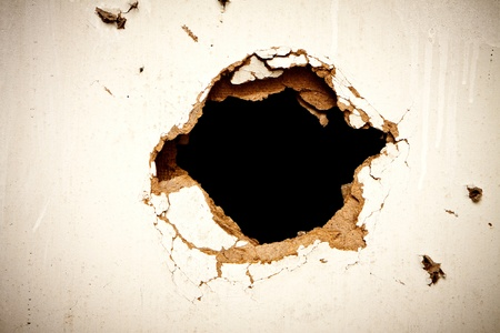Hole in the fibreboard on black background