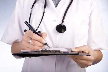 Healthcare professional, doctor or nurse, writing with a fountain pen on a paper over a folder Stock Photo - 13247054