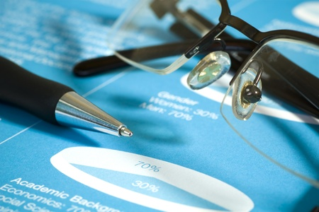 Fountain pen and glasses on stock chart on blue report  Shot in studio  photo