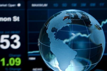 Glass globe over stock data on computer screen photo